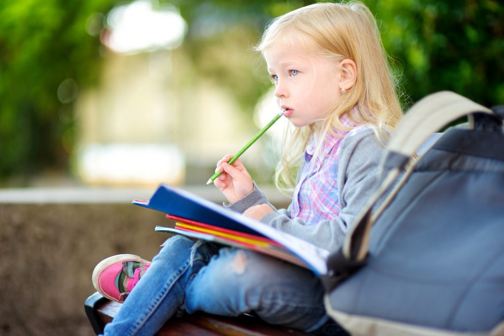Adorable little schoolgirl studying outdoors on bright autumn day. Young student doing her homework. Education for small kids.